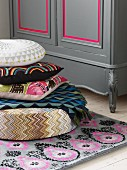 Colourful patterned cushions on rug next to grey cupboard with pink accents