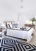 Bright bedroom with double bed and blue and white carpet