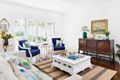 Elegant living room with blue upholstered armchairs, antique furniture and country house flair