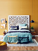 Double bed with ornate bed head and turquoise bed linen against an ocher wall