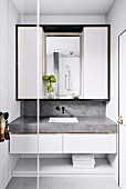Bathroom installation with marbled vanity top and white wall cabinet with black frame