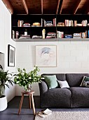 Metal hanging shelf for books on a cozy anthracite-colored upholstered couch in a 70s living room