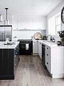 weiße Einbauküche mit schwarzem Küchenblock