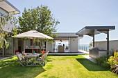 Architektenhaus mit Garten, Sitzplatz unter Sonnenschirm auf Rasenfläche, Außenküche und Meerblick