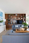 Elegant living area with shelves and cozy blue-gray upholstered furniture