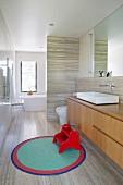 Elegant designer bathroom with natural stone cladding and elegant washbasin base