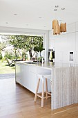 Designer kitchen with bar stool and kitchen island made of natural stone