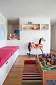 Play area with nostalgic rocking horse, wooden toys and built-in bench