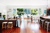 Offener Wohnraum mit Edelholzparkett, Loungebereich und Essplatz vor offenen Terrassentüren mit Gartenblick