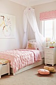 Romantic girl's room with canopy bed and pink duvet