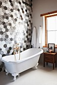 Vintage-style bathtub against black and white hexagonal wall tiles