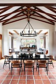 Black dining table and chairs on terracotta floor tiles in open-plan interior