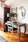 Rococo desk, table lamp and chair below pictures and mirror on wall