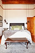 Double bed and bedroom bench made from exotic wood in high-ceilinged bedroom with pendant lamps