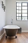Free-standing bathtub on wooden floor in purist bathroom