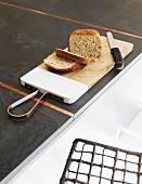 Schneidebrett mit Brot und Messer auf anthrazitfarbener Küchenarbeitsplatte