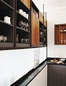 Crockery and glasses on elegant fitted shelves above serving hatch