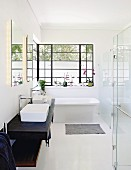Free-standing bathtub and metal windows in elegant bathroom