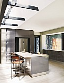 Free-standing counter in grey kitchen with light falling through skylight