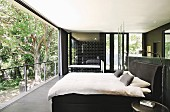 Bedroom with ensuite bathroom and sliding glass wall with view of garden