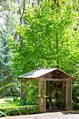 Holzpavillion mit Satteldach und Gitterstruktur unter Ahornbaum