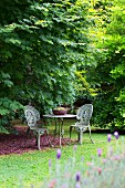 Romantic garden space with table and two decorated iron garden chairs in antique style