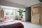 DIY sliding door made from various wooden panels and houseplant on plain wooden table in bedroom