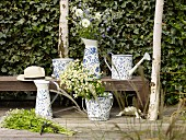 Jugs, watering can and bucket with rustic, floral patterns on terrace