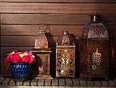 Oriental, metal lanterns and blue ceramic pot of roses