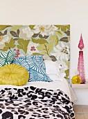 Ausschnitt eines Bettes mit floral gemustertem Kopfteil und Kissen