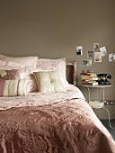 Shiny bedspread and scatter cushions in pastel pinks and bedside table below postcards on grey wall