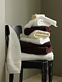 White an dark brown towels stacked on vintage wooden chair