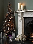Christmas baubles on hearth and lit candles on mantelpiece next to decorated Christmas tree