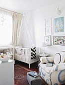 White cot and comfortable armchair in nursery