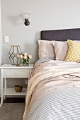 Feminine bedroom with white bedside table and bouquet of roses