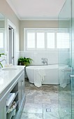Elegant bathroom with free-standing white bathtub, natural stone tile floor and green plants
