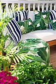 Sunny terrace with green plants, pouf and cozy upholstered sofa with various pillows