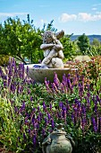 Angel figure in the fountain and frog prince in the lavender bed