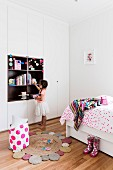 Children's room with bed and floor-to-ceiling wardrobe, girl in front of alcove