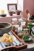 Storage jars, ceramic crockery and pastries on wicker tray