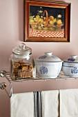 Porcelain bowls and glass jar on wall-mounted metal shelf