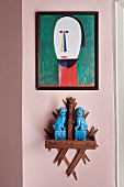 Blue animal figurines on wooden bracket and modern portrait of man on pink wall