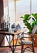 Candlesticks and crockery on side table next to cane chair and houseplant