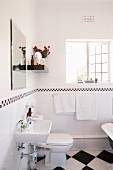 Open lattice window and black and white tiles in renovated bathroom of period apartment