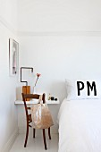 White wall-mounted shelf used as bedside table and vintage chair with bag on backrest in period apartment