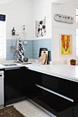 Schwarze Einbauküche mit weisser Arbeitsplatte und Spritzschutz aus hellblauen Wandfliesen