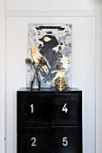 Painting of bird above gold skull under glass cover on top of black locker