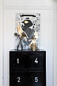 Gemälde mit Vogelmotiv und goldglänzender Totenkopf unter Glashaube auf schwarzem Schrank