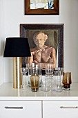 Collection of glasses and table lamp in front of framed portrait of man
