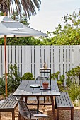 Parasol and wooden outdoor furniture on terrace in front of picket fence